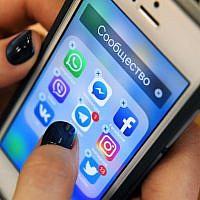 Une femme tient un smartphone avec les icônes des réseaux sociaux  Facebook, Instagram, Twitter et autres à Moscou, le 23 mars 2018. (Crédit : Kirill KUDRYAVTSEV/AFP)