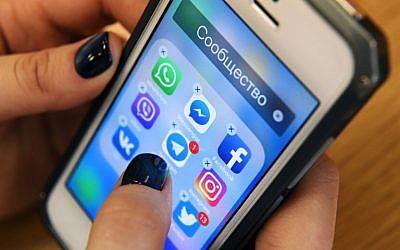 Une femme tient un smartphone avec les icônes des réseaux sociaux  Facebook, Instagram, Twitter et autres à Moscou, le 23 mars 2018 (Crédit : Kirill KUDRYAVTSEV/AFP