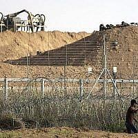 Un Palestinien utilise une fronde pour jeter une pierre aux soldats israéliens de l'autre côté de la frontière lors d'affrontements à l'est de Gaza City, le 13 juillet 2018 (Crédit : AFP PHOTO / MAHMUD HAMS)