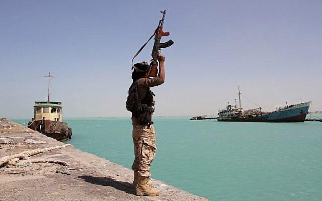Un membre des forces progouvernementales lève son arme dans le port de Mokha, à l'ouest du Yémen, alors que les troupes soutenues par l'Arabie saoudite avancent pour chasser les rebelles Houthis chiites de la région de la mer Rouge, le 8 févrer 2017. (Crédit : AFP/Saleh al-Obeidi)