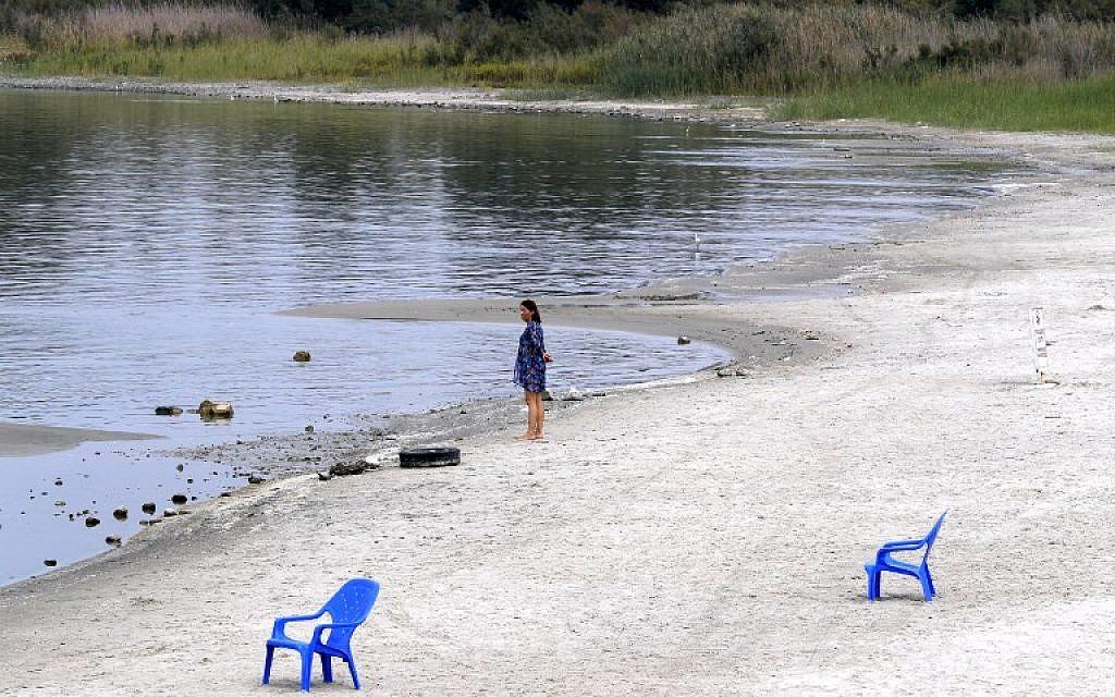 Une femme se tient sur la plage de sable du lac de Tibériade., le 8 ocotbre 2018 Les étendues de sable  sont apparues à cause d'une baisse de niveau de l'eau, attribuée à une surexploitation des ressources. (Crédit : JACK GUEZ / AFP)
