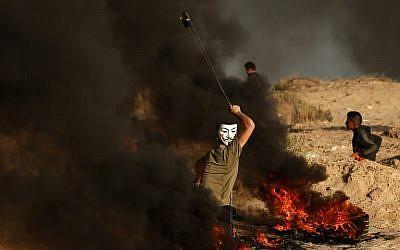 Photo d'illustration : Un Palestinien utilise une fronde pour jeter des pierres lors d'un affrontement près de la frontière avec Israël, sur une plage, à Beit Lahia, dans le nord de la bande de Gaza, le 28 octobre 2018 (Crédit :Mahmud Hams/AFP)