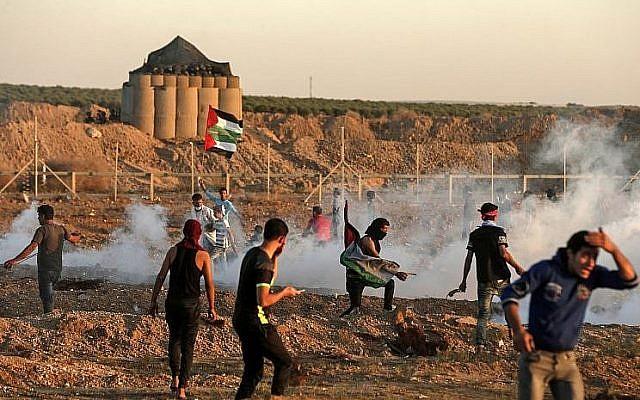 Les Palestiniens réagissent aux gaz lacrymogènes lancés par les soldats israéliens au cours d'affrontements survenus à l'est de Gaza City, près de la frontière entre Gaza et Israël, le 2 novembre 2018 (Crédit : Mahmud Hams/AFP)