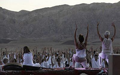 Des yogis, israéliens et étrangers, participent au festival annuel de yoga d'Arava dans le secteur des anciennes mines de cuivre dans la vallée de Timna, dans la région d'Arava, dans le sud d'Israël, le 2 novembre 2018 (Crédit : MENAHEM KAHANA / AFP)