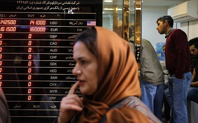 Une femme passe devant un bureau de change dans le grand bazar de la capitale iranienne, le 3 novembre 2018. (Crédit : ATTA KENARE / AFP)