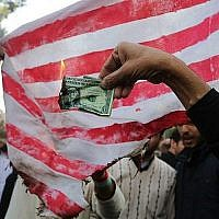 A la veille de la reprise des sanctions de Washington, les manifestants iraniens brûlent un dollar et un drapeau américain durant une manifestation dans la capitale iranienne de Téhéran marquant l'anniversaire de la prise d'assaut de l'ambassade américaine par des étudiants qui avait entraîné une prise d'otage, en 1979, le 4 novembre 2018 (Crédit : ATTA KENARE / AFP)