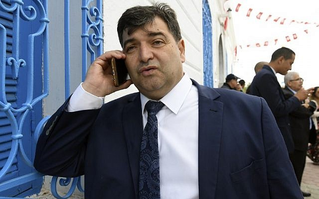 Sur cette photo prise le 2 mai 2018, on voit René Trabelsi au téléphone devant la synagogue de la Ghriba de l'île de villégiature tunisienne de Djerba. Trabelsi, qui appartient à la communauté juive de Tunisie, a été nommé ministre du Tourisme lors du dernier remaniement gouvernemental, le 5 novembre 2018. (Crédit : FETHI BELAID / AFP)