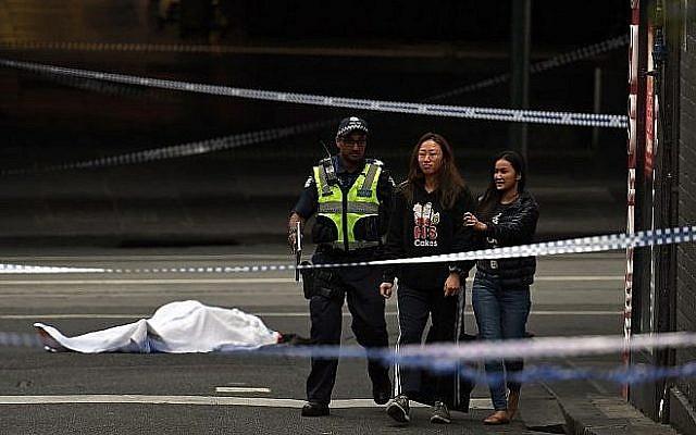un policier écarte les passants de la scène d'une attaque au couteau, devant le corps de la victime, recouvert d'un drap blanc, à Melbourne, le 9 novembre 2018 (Crédit : WILLIAM WEST / AFP)