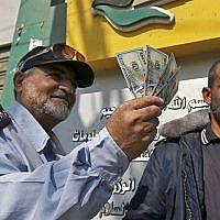 Un Palestinien montre son argent après avoir reçu son salaire à Rafah dans le sud de la bande de Gaza, le 9 novembre 2018 (Crédit : Said Khatib/AFP)