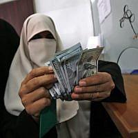 Une Palestinienne compte son argent après avoir reçu son salaire à Rafah, dans le sud de la bande de Gaza, le 9 novembre 2018. (Said Khatib/AFP)