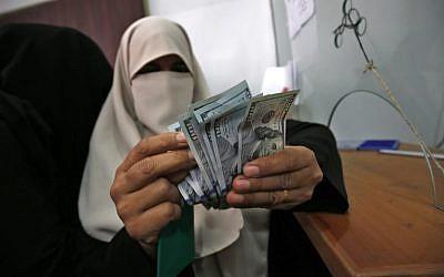 Une Palestinienne compte son argent après avoir reçu son salaire à Rafah, dans la bande de Gaza, le 9 novembre 2018 (Crédit :  Said Khatib/AFP)