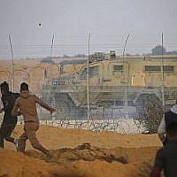 Des Palestiniens jettent des pierres sur un véhicule militaire pendant une manifestation à proximité de la frontière entre Israël et Khan Yunès dans le sud de la bande de Gaza, le 9 novembre 2018 (Crédit : Said KHATIB / AFP)