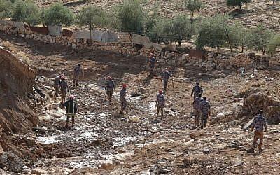 Des équipes de secours jordaniennes à la recherche de personnes disparues à la suite d'inondations soudaines dans la ville de Madaba, près de la capitale jordanienne, le 10 novembre 2018. (Crédit : KHALIL MAZRAAWI / AFP)