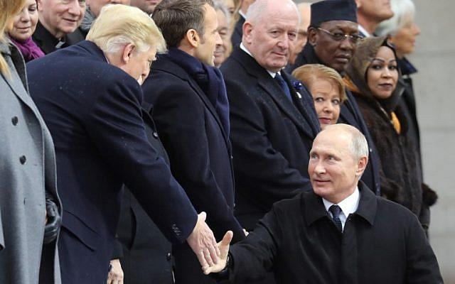Poignée de mains entre le président russe Vladimir Poutine et son homologue américain Donald Trump, à l'Arc de Triomphe  à l'occasion des cérémonies du centenaire de la Première guerre mondiale., le 11 novembre 2018. (Crédit :  Ludovic MARIN / POOL / AFP)