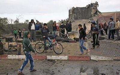 Des Palestiniens près des décombres d'un immeuble qui aurait été détruit par une frappe israélienne à Khan Younès, dans le sud de la bande de Gaza, le 12 novembre 2018 (Crédit : SAID KHATIB / AFP)