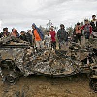 Des Palestiniens autour des décombres d'une voiture qui aurait été détruite par une frappe israélienne à Khan Younès, dans le sud de la bande de Gaza, le 12 novembre 2018 (Crédit : SAID KHATIB / AFP)