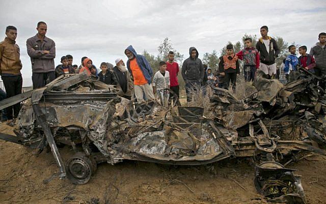 Des Palestiniens autour des décombres d'une voiture qui aurait été détruite par une frappe israélienne à Khan Younès, dans le sud de la bande de Gaza, le 12 novembre 2018. (Crédit : SAID KHATIB / AFP)