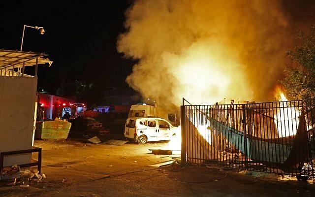Les forces de sécurité et les pompiers israéliens se rassemblent près d'un bâtiment incendié après avoir été touché par une roquette tirée depuis l'enclave palestinienne dans la ville de Sdérot, dans le sud du pays, le 12 novembre 2018. (Crédit : Jack GUEZ / AFP)