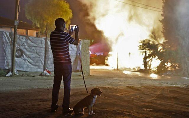 Un homme observe un bâtiment qui a été incendié après avoir été touché par une roquette tirée depuis la bande de Gaza, dans la ville de Sdérot, dans le sud d'Israël, le 12 novembre 2018. (Crédit : Menahem KAHANA / AFP)