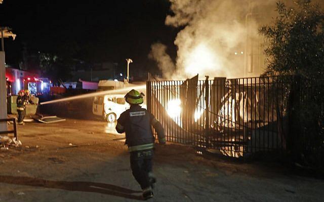 Les forces de sécurité et les pompiers israéliens se rassemblent près d'un bâtiment incendié après avoir été touché par une roquette tirée depuis la bande de Gaza, dans la ville de Sderot, dans le sud du pays, le 12 novembre 2018. (Crédit : Menahem KAHANA / AFP)