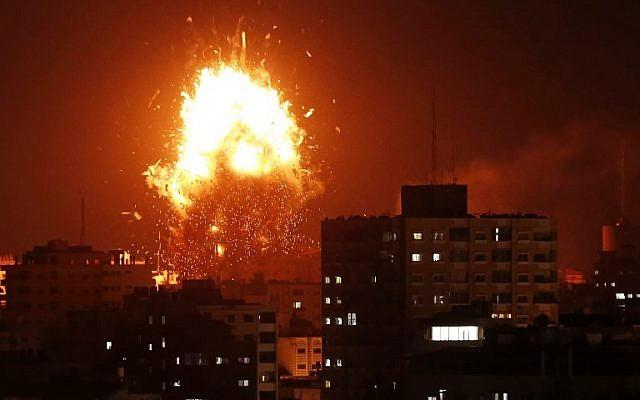 Une boule de feu au-dessus du bâtiment abritant la chaîne de télévision Al-Aqsa dirigée par le Hamas dans la bande de Gaza lors d'une frappe aérienne israélienne le 12 novembre 2018. (Crédit : MAHMUD HAMS / AFP)