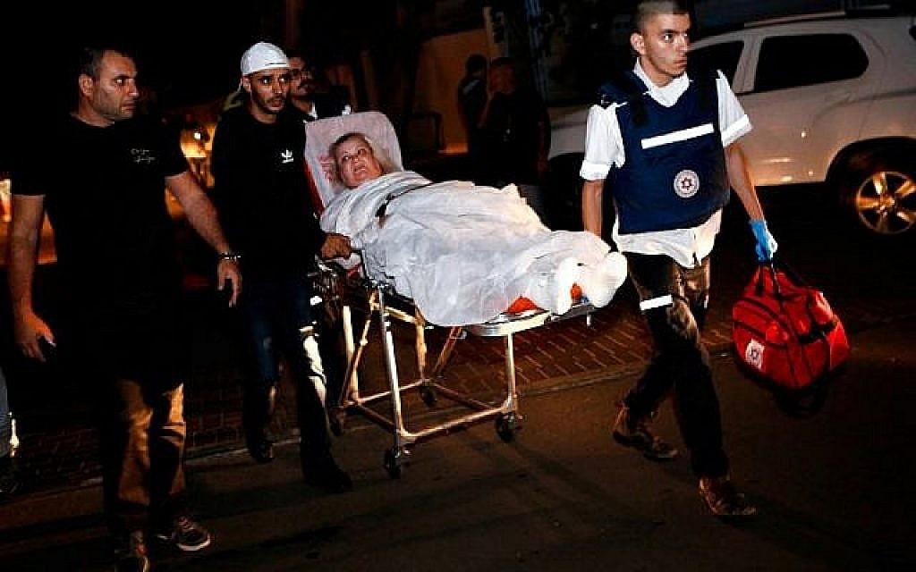 Une femme israélienne blessée, évacuée de son appartement incendié après avoir été touché par une roquette tirée depuis la bande de Gaza, est escortée à l'hôpital sur une civière dans la ville d'Ashkelon, dans le sud d'Israël, le 12 novembre 2018. (Crédit : GIL COHEN-MAGEN / AFP)