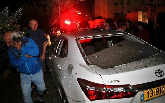 Deux hommes marchant devant un véhicule touché par une roquette tirée depuis la bande de Gaza, dans la ville d'Ashkelon, dans le sud d'Israël, le 12 novembre 2018. (Crédit : GIL COHEN-MAGEN / AFP)