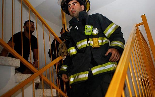 Un pompier israélien évacue un immeuble d'Ashkelon touché par une roquette lancée depuis Gaza, le 12 novembre 2018. (Crédit : GIL COHEN-MAGEN / AFP)