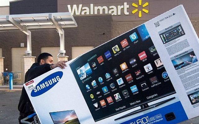 Sur cette photo prise le 28 novembre 2014, Umer Gonzalez, adepte des soldes du Black Friday, emporte son téléviseur grand écran Samsung acheté dans un Walmart à Fairfax, en Virginie. (Photo par Paul J. RICHARDS / AFP)