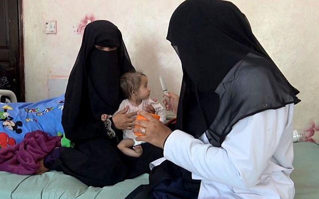 Une mère yéménite tient son enfant malnutri pendant qu'une infirmière tente de le nourrir, dans hôpital de Taez au Yémén, le 19 novembre 2018. (Crédit : Marzooq AL-JABIRY / AFP)