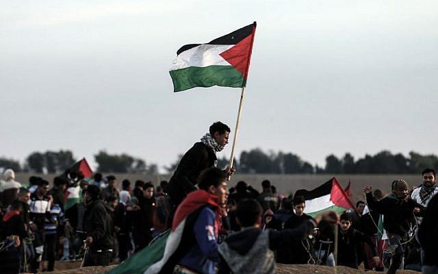Des émeutiers palestiniens brandissent des drapeaux dans la banlieue est de Gaza City, le 23 novembre 2018. (Crédit : MAHMUD HAMS / AFP)