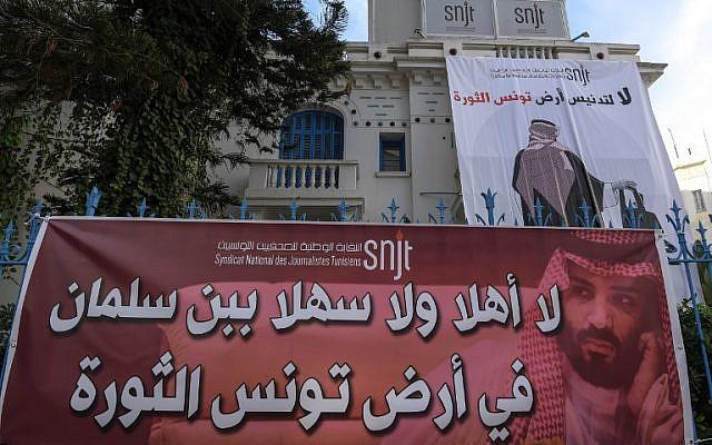 """Une affiche géante placardée sur le local du Syndicat national des journalistes tunisien (SNJT), montrant un Saoudien de dos, une tronçonneuse à la main et la phrase """"Non à la profanation de la Tunisie, pays de la révolution"""", pour protester contre la venue du prince héritier saoudien dans le contexte de l'affaire Khashoggi, à Tunis, le 26 novembre 2018. (Crédit : FETHI BELAID / AFP)"""