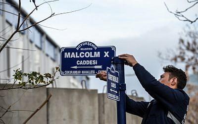 un employé municipal d'Ankara remplace le panneau de la rue de l'ambassade américaine en Turquie, le 29 novembre 2018. (Crédit : AFP)