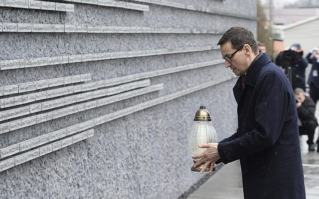 Le Premier ministre polonais Mateusz Morawiecki met une bougie sur un site commémorant des Polonais qui avaient sauvé des Juifs pendant la Shoah, au musée de la famille Ulma des Polonais qui ont secouru des Juifs à Markowa, en Pologne, le 2 février 2018 (Crédit : AP/Alik Keplicz)
