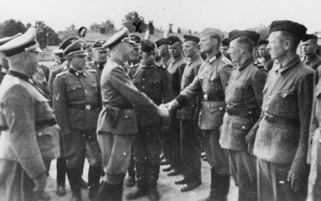 Sur cette photo de 1942 fournie par le bureau du procureur de Hambourg, Heinrich Himmler, au centre gauche, serre la main aux nouvelles recrues du camp de concentration de Trawniki dans la Pologne occupée par les nazis (Crédit :  bureau du procureur de Habourg via le musée du mémorial de la Shoah des Etats-Unis via l'AP)