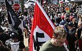 Illustration: un suprématiste blanc portant un drapeau nazi dans le parc Emancipation à Charlottesville, en Virginie, le 12 août 2017. (Crédit : AP / Steve Helber)