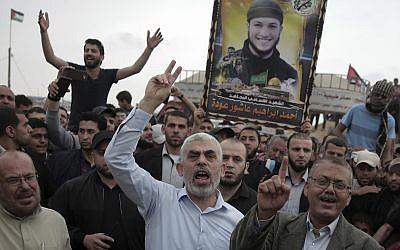 Le leader du Hamas à Gaza, Yahya Sinwar, au centre, scande des slogans avec des manifestants durant sa visite à la frontière avec la bande de Gaza, le 20 avril 2018 (Crédit : AP Photo/Khalil Hamra)