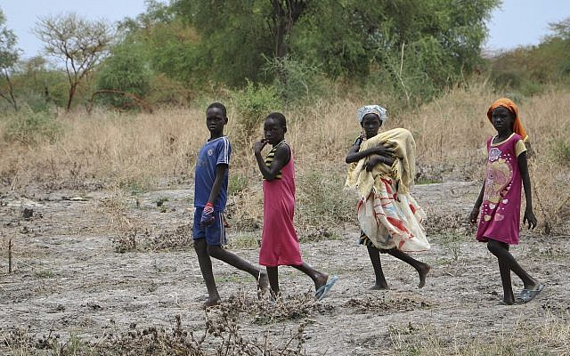 Des fillettes se dirigent vers un dispositif du Programme alimentaire mondial, au nord de Kandak, au Sud-Soudan, le 2 mai 2018. (Crédit : Sam Mednick/AP)