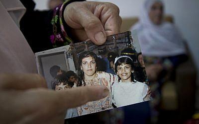 Dans cette photo du 8 août 2018, Fadwa Tlaib, une tante de Rashida Tlaib, désigne la jeune Rashida dans une photo de 1987 avec sa mère Fatima et son frère Nader, dans la maison familiale du village de Beit Ur al-Foqa, en Cisjordanie. (AP/Nasser Nasser Nasser)