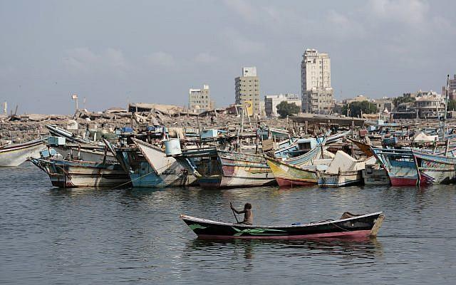 Un bateau de pêcheurs navigue devant le port d'Hodeida. En arrière-plan, les immeubles détruits par la coalition soutenue par l'Arabie saoudite et les Emirats arabes unis, le 28 septembre 2018 (Crédit : AP/Hani Mohammed)