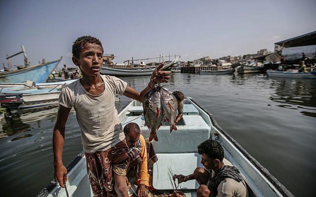 Des enfants pêchent au port d'Hodeida, au Yémen, le 29 septembre 2018. (Crédit :  AP/Hani Mohammed)