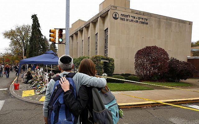 La population rend hommage aux 11 personnes tuées le 27 octobre 2018, devant un mémorial de fortune à l'extérieur de la synagogue Tree of Life, dans le quartier Squirrel Hill de Pittsburgh, le jeudi 1er novembre 2018. (Crédit : AP Photo/Gene J. Puskar)
