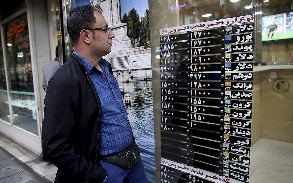 Un Iranien regarde le taux de change à travers la vitrine d'une boutique du centre de Téhéran, en Iran, le 5 novembre 2018 (Crédit : AP/Ebrahim Noroozi)