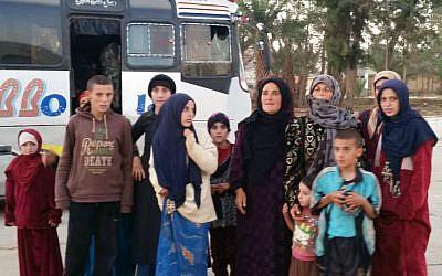 Cette photo de l'agence SANA montre des femmes et des enfants libérés par l'Etat islamique dans la région de Hamima, à l'est de Palmyre, en Syrie, le 8 novembre 2018 (Crédit :  SANA via AP)