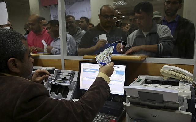 Un employé du gouvernement du Hamas palestinien signe pour recevoir 60 % de son salaire alors que les autres fonctionnaires font la queue, au principal bureau de poste de Gaza, le 9 novembre 2018 (Crédit :  AP/Adel Hana)