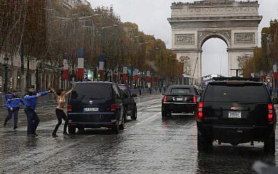 La police française arrête une militante dénudée qui se précipite vers le convoi du Donald Trump, à Paris, le 11 novembre 2018. (Crédit : AP/Jacquelyn Martin)