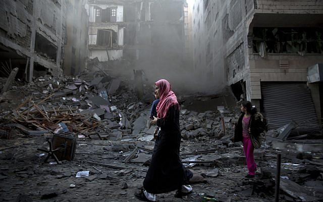 Une femme palestinienne passe à proximité d'un immeuble résidentiel détruit, frappé par des frappes aériennes israéliennes dans la ville de Gaza, le mardi 13 novembre 2018. (Crédit : AP / Khalil Hamra)