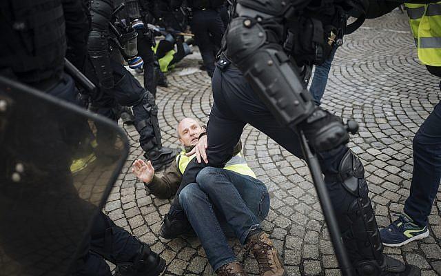 """Les """"gilets jaunes"""" aux prises avec la police anti-émeutes sur l'avenue des Champs-Elysées à Paris, le 24 novembre 2018 (Crédit : AP Photo/Kamil Zihnioglu)"""