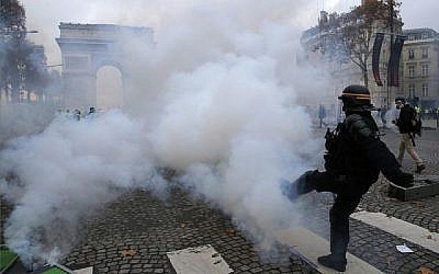 """Un policier anti-émeutes sur l'avenue des Champs Elysées, près de l'Arc de Triomphe, lors d'une mobilisation des """"Gilets Jaunes"""" contre la hausse du coût de la vie à Paris, le 24 novembre 2018 (Crédit : AP Photo/Michel Euler)"""