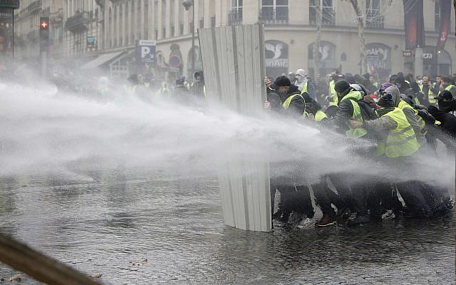 """Les """"Gilets jaunes"""" utilisent une barrière pour se protéger des canons à eau des policiers pendant une manifestation sur les Champs Elysées pour dénoncer la hausse des taxes sur les carburants,  le 24 novembre 2018 (Crédit : AP Photo/Kamil Zihnioglu)"""